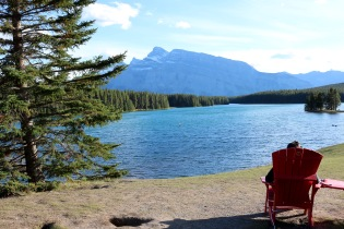 Adam enjoying the view of Two Jack Lake in an Adirondack chair in Banff National Park.