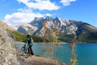 Amanda walking her bike along a trail on Lake Minnewanka in Banff National Park.