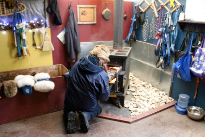 Our Musher, Gerald stoking the fire in the Musher's Den - Bluesky Bed & Sled, Churchill, MB